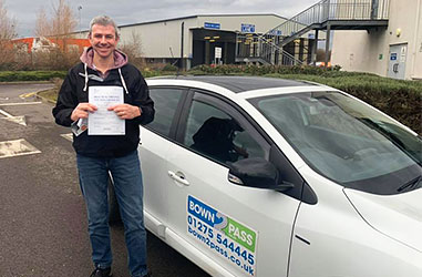 Driving student passing driving test - Student test passed - Standing in front of driving school vehicle and displaying certificate